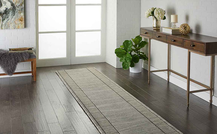 Home entryway with white brick walls, potted green house plant, runner area rug on engineered wood flooring.