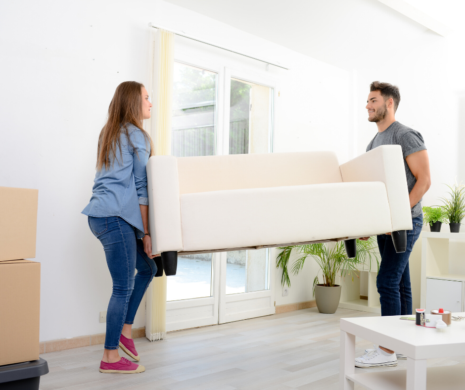 Man and woman carrying white couch out of room